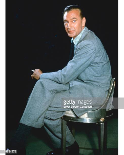 Gary Cooper , US actor, smoking a cigarette while sitting in a chair, wearing a light grey suit, in a studio portrait, circa 1955.