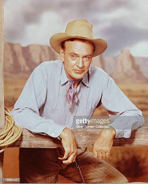 Gary Cooper , US actor, wearing a cowboy hat, blue shirt and lilac neckerchief, leaning against a fence in a studio portrait, with a western...