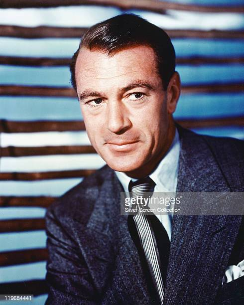 Gary Cooper , US actor, wearing a dark blue jacket, white shirt and black-and-white striped tie, in a studio portrait, circa 1950.