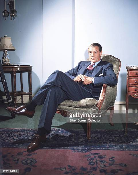 Gary Cooper , US actor, wearing a dark blue suit, with a light blue shirt and a red tie, sitting in an armchair, circa 1945.