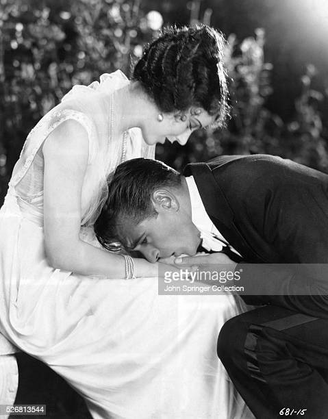 Gary Cooper who plays the role of Gale Price kneels and kisses the hand of Christine Charteris played by Fay Wray in the 1928 film The Legion of the...