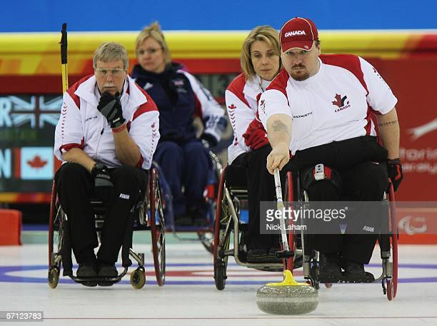 Gary Cormack watches team mate Chris Daw of Canada play his next shot while competing in the Wheelchair Curling Final between Great Britain and...