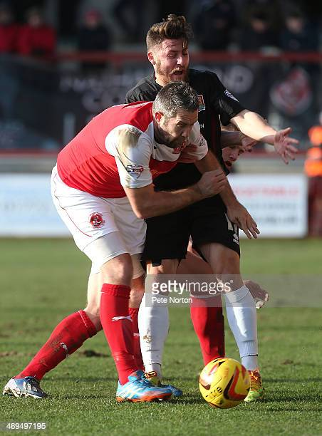 Gary Deegan of Northampton Town contests the ball with Jon Parkin of Fleetwood Town during the Sky Bet League Two match between Fleetwood Town and...