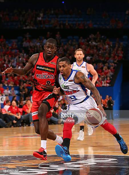 Gary Ervin of the 36ers brings the ball down against James Ennis of the Wildcats the court during the round one NBL match between the Perth Wildcats...