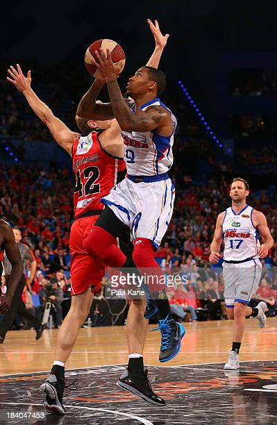 Gary Ervin of the 36ers lays up against Shawn Redhage of the Wildcats during the round one NBL match between the Perth Wildcats and the Adelaide...