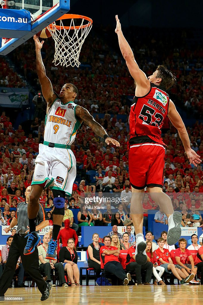 Gary Ervin of the Crocodiles lays up against Damian Martin of the Wildcats during the round 16 NBL match between the Perth Wildcats and the Townsville Crocodiles at Perth Arena on January 25, 2013 in Perth, Australia.