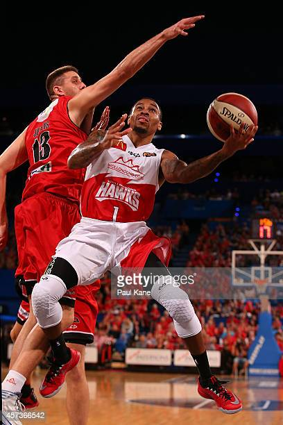 Gary Ervin of the Hawks drives to the basket against Tom Jervis of the Wildcats during the round two NBL match between the Perth Wildcats and the...