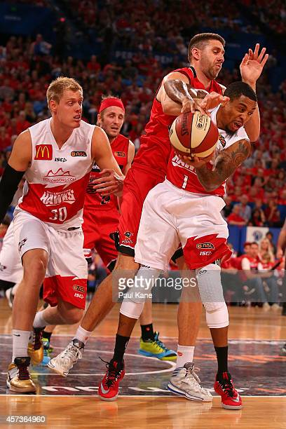 Gary Ervin of the Hawks gets fouled by Tom Jervis of the Wildcats during the round two NBL match between the Perth Wildcats and the Wollongong Hawks...