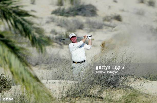 Gary Evans of England plays from the scrub on the eighth hole during the second round of the 2004 Dubai Desert Classic played at the Emirates Golf...