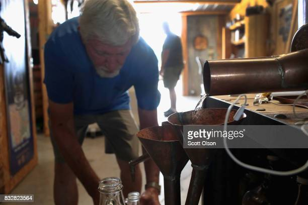 Gary Fromm collects moonshine as it runs from the still at Casey Jones Distillery on August 16, 2017 in Hopkinsville, Kentucky. To celebrate the...