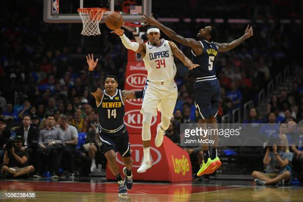 Gary Harris of the Denver Nuggets and Will Barton of the Denver Nuggets guard Tobias Harris of the Los Angeles Clippers during the season opening...