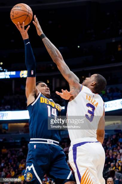 Gary Harris of the Denver Nuggets attempts a jump shot over Trevor Ariza of the Phoenix Suns during the second half at Pepsi Center on October 20...