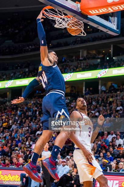 Gary Harris of the Denver Nuggets dunks the ball over Trevor Ariza of the Phoenix Suns during the second half at Pepsi Center on October 20 2018 in...
