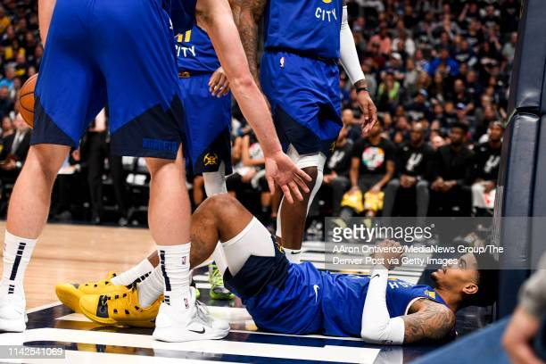 Gary Harris of the Denver Nuggets lies on the ground after taking a hard foul against the San Antonio Spurs during the fourth quarter of the Spurs'...