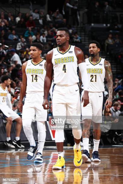 Gary Harris of the Denver Nuggets Paul Millsap of the Denver Nuggets and Wilson Chandler of the Denver Nuggets look on during the game against the...