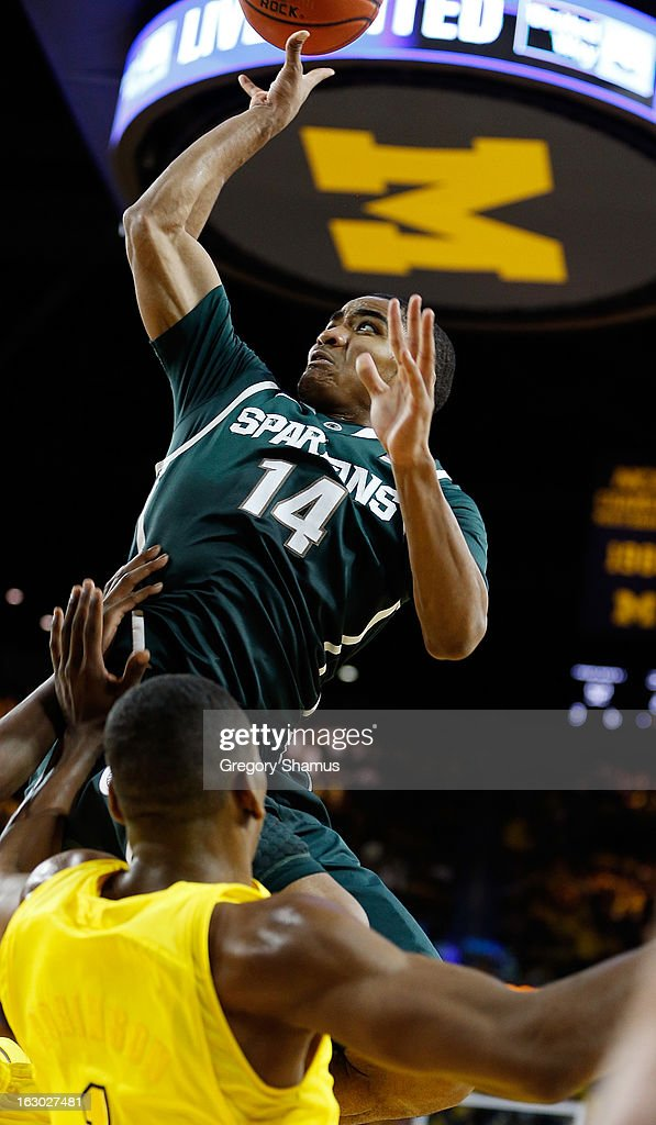 Gary Harris #14 of the Michigan State Spartans gets off a second half shot over Glenn Robinson III #1 of the Michigan Wolverines at Crisler Center on March 3, 2013 in Ann Arbor, Michigan. Michigan won the game 58-57.