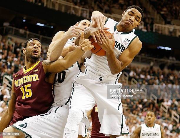 Gary Harris of the Michigan State Spartans grabs a first half rebound next to Maurice Walker of the Minnesota Golden Gophers at the Jack T Breslin...