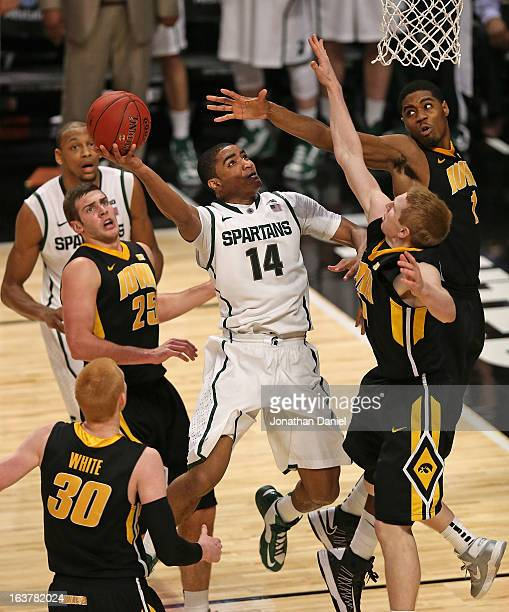 Gary Harris of the Michigan State Spartans shoots against Aaron White, Eric May, Melsahn Basabe and Mike Gesell of the Iowa Hawkeyes during a...