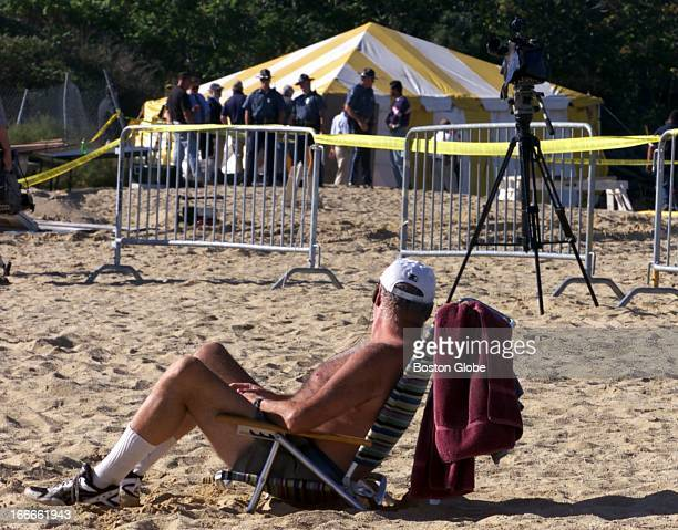 Gary Hillis Of Dorchester Lounges On The Beach While Police Search Under Tent For Bodies