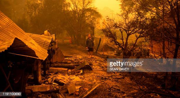 TOPSHOT Gary Hinton stands amongst rubble after fires devastated the New South Wales town of Cobargo on December 31 2019 Thousands of holidaymakers...