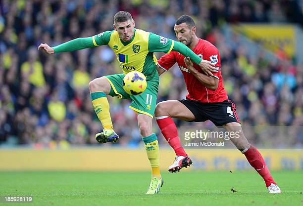 Gary Hooper of Norwich City vies with Steven Caulker of Cardiff City during the Barclays Premier League match between Norwich City v Cardiff City at...