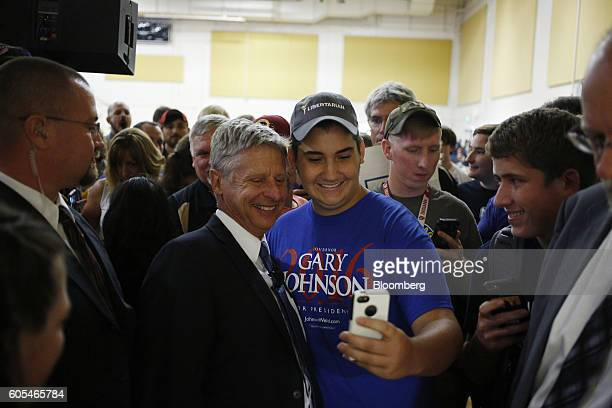 Gary Johnson, 2016 Libertarian presidential nominee, center left, poses for a photograph with a supporter during a campaign event at Purdue...