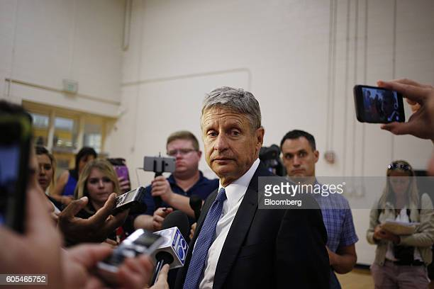 Gary Johnson, 2016 Libertarian presidential nominee, center, speaks with reporters following a campaign event at Purdue University in West Lafayette,...