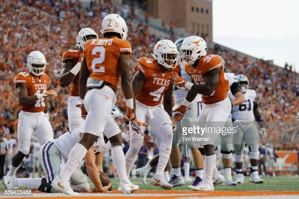 Gary Johnson of the Texas Longhorns congratulates DeShon Elliott after a tackle of Jesse Ertz of the Kansas State Wildcats in the first quarter at...