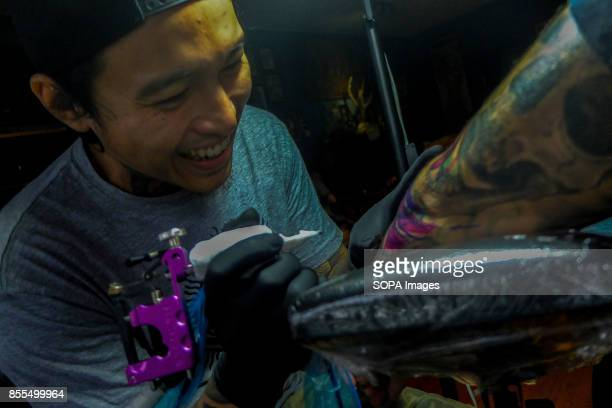 Gary Jones is seen while tattooing a client inside his shop Gary Jones is one of the Kadazan talented tattoo artist from Borneo He had almost 10...