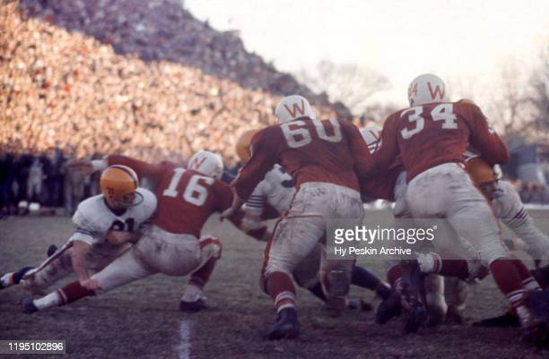 Gary Kolb of the Illinois Fighting Illini tries to block as Jerry Stalcup Bob Zeman and Billy Hobbs of the Wisconsin Badgers go for the tackle during...