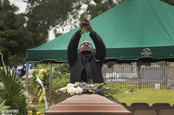 Gary L Washington son of Emanuel AME Church shooting victim Ethel Lance holds a rose up as he prays during her burial at the Emanuel AME Church...