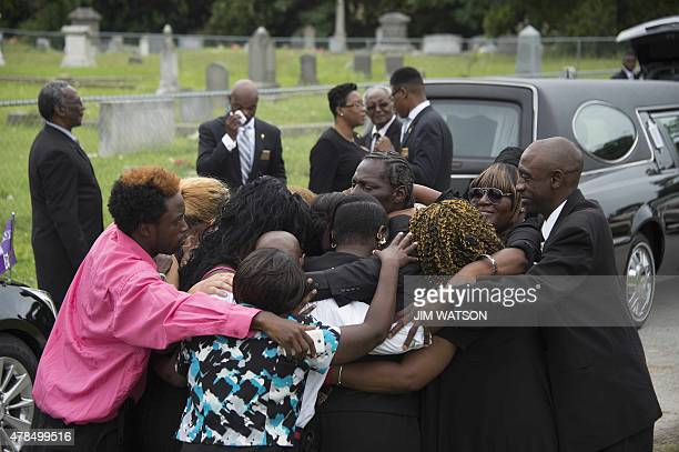 Gary L Washington son of Emanuel AME Church shooting victim Ethel Lance is hugged by members of his family during his mother's burial at the Emanuel...