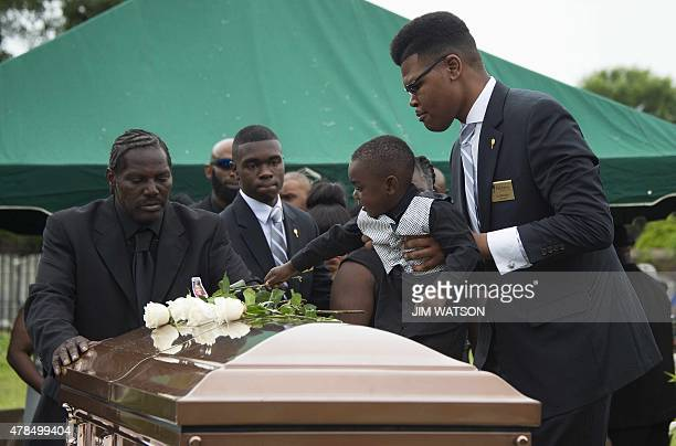 Gary L Washington son of Emanuel AME Church shooting victim Ethel Lance watches as family members place roses upon her casket during the burial at...