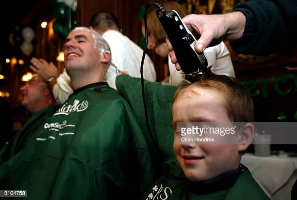 Gary Ludden Jr closes his eyes while getting his hair shaved during a St Baldrick's Day event at Jim Brady's Pub March 17 2004 in New York City The...