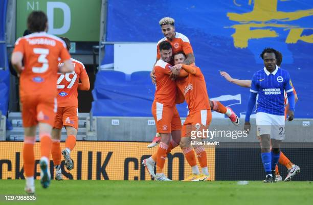 Gary Madine of Blackpool celebrates with teammates Jordan Gabriel and Jerry Yates after scoring his team's first goal during The Emirates FA Cup...