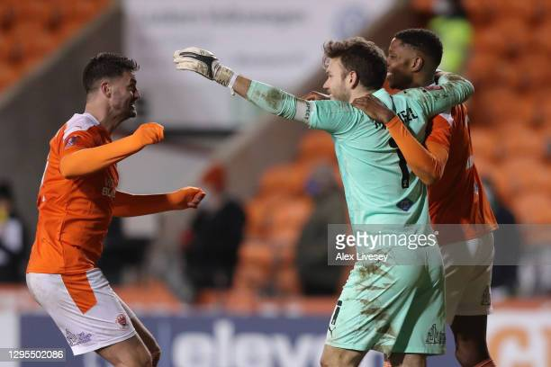 Gary Madine of Blackpool embraces teammate Chris Maxwell after his save wins the match after the FA Cup Third Round match between Blackpool and West...