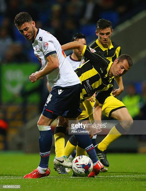 Gary Madine of Bolton Wanderers and Phil Edwards of Burton Albion battle for the ball during the Capital One Cup first round match between Bolton...
