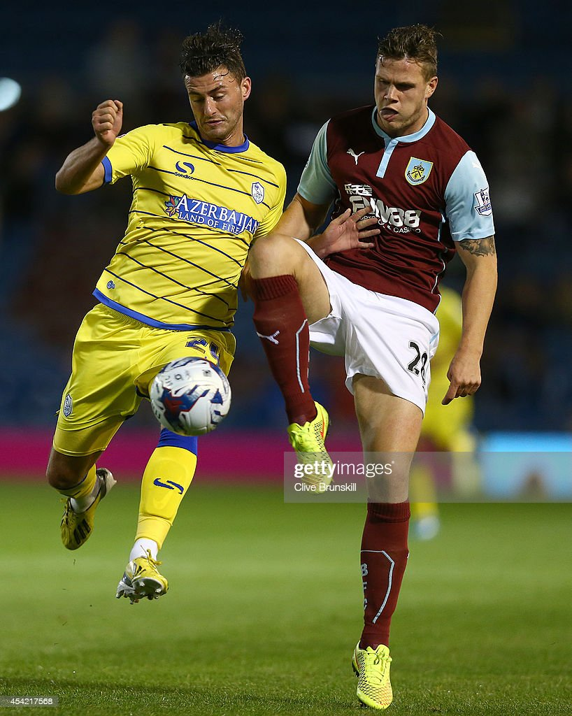 Gary Madine of Sheffield Wednesday in action with Kevin Long of Burnley during the Capital One Cup Second Round match between Burnley and Sheffield Wednesday at Turf Moor on August 26, 2014 in Burnley, England.