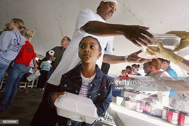 Gary McKendall and his daughter Aaliyah receive a free Thanksgiving meal of turkey and stuffing donated by a Christian group on November 24 2005 in...