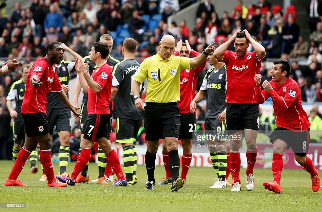 Gary Medel (R) and Steven Caulker of Cardiff City (2R) react as referee Howard Webb awards a penalty kick to Stoke City during the Barclays Premier League match between Cardiff City and Stoke City at Cardiff City Stadium on April 19, 2014 in Cardiff, Wales.