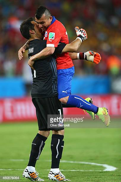 Gary Medel of Chile jumps into the arms of goalkeeper Claudio Bravo after a goal in the first half during the 2014 FIFA World Cup Brazil Group B...