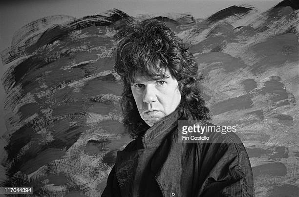 Gary Moore British blues rock guitarist and singer poses in front of a painting in a studio portrait in 1986