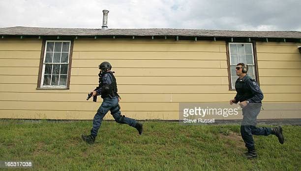 Gary Moxam right chases PC Mark Drozdzowski through the course to guide him and assess penalties The Toronto's Emergency Task Force trains with four...