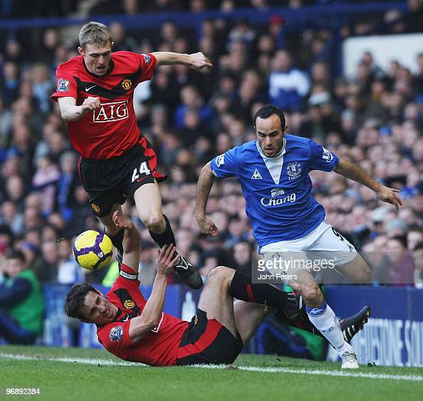 Gary Neville and Darren Fletcher of Manchester United clash with Landon Donovan of Everton during the FA Barclays Premier League match between...