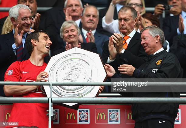 Gary Neville of Manchester United passes the trophy to manager Sir Alex Ferguson as they are victorious on penalty kicks during the FA Community...