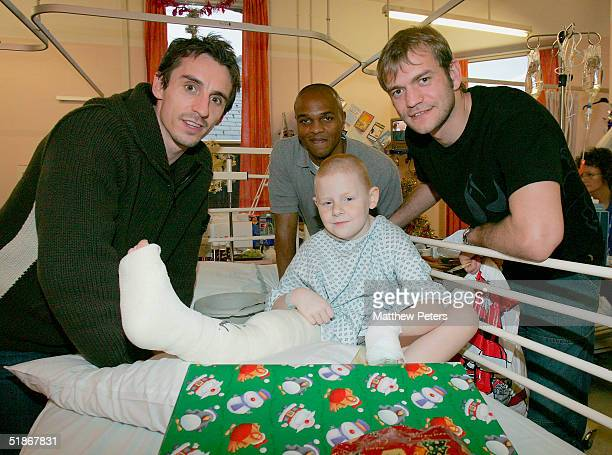 Gary Neville, Quinton Fortune and Roy Carroll pose with Reece Prendergast, aged nine, during the annual players' Christmas visits to hospitals at...