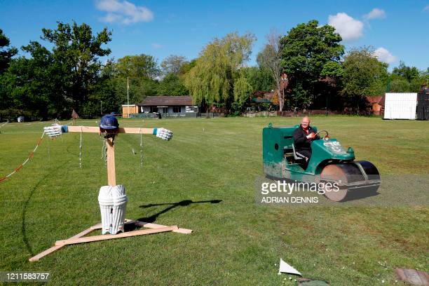 Gary O'Hara, volunteer groundsman and semi-retired player for Crown Taverners in the Hampshire cricket league, drives a roller on the ground past a...