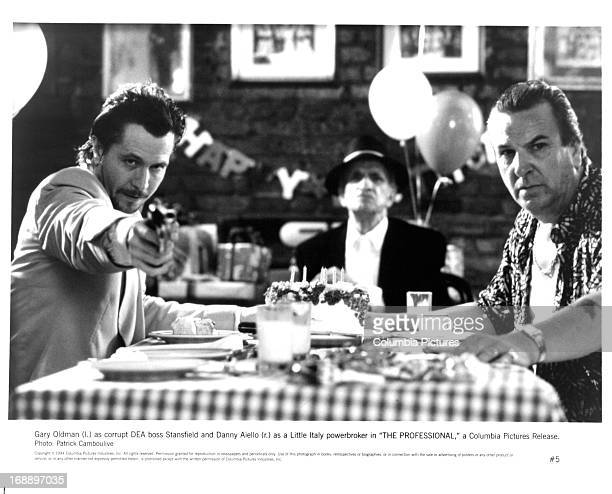 Gary Oldman points a gun next to Danny Aiello at a table in a scene from the film 'Léon The Professional' 1994