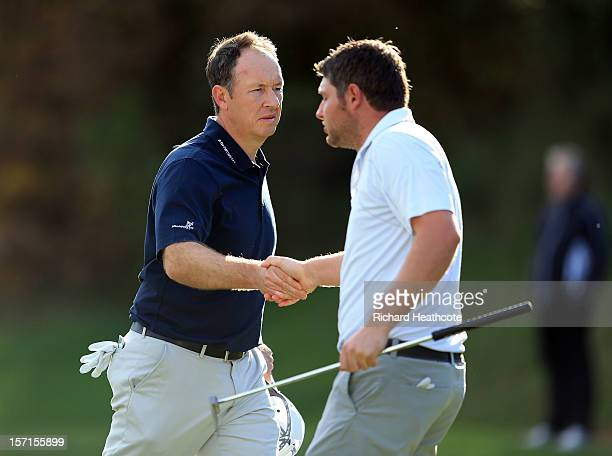 Gary Orr of Scotland shakes hands with George Murray of Scotland as they both drop shots at the 18th hole but Orr manages to retain his card by a...