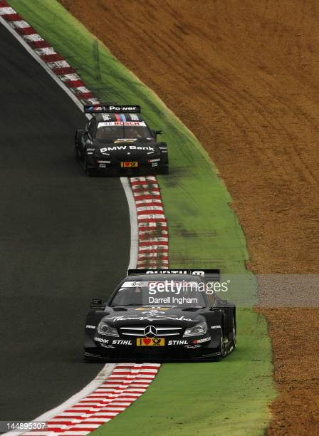 Gary Paffett of Great Britain driving the Thomas Sabo Mercedes AMG C Coupe leads Bruno Spengler of Canada in the BMW Team Schnitzer BMW M3 DTM down...